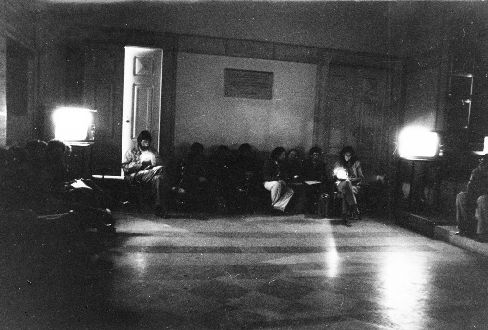 "Performance at the opening of ""The Promised Land"", SNBA, 1980. Four performers read simultaneously sitting next to one of the four monitors."